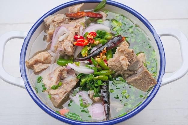 Pikantna zupa z kości wieprzowej w stylu tajskim to klarowna zupa wieprzowa z dużymi kośćmi wieprzowymi, ozdobiona chili i tajskimi ziołami