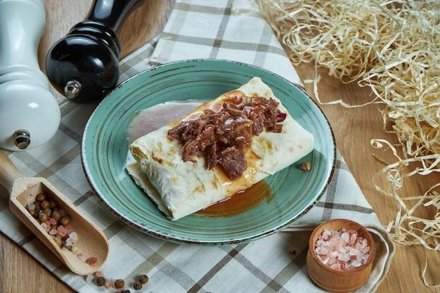 Pikantne burrito lub shawarma na niebieskim talerzu z tradycyjną gotowaną, miękką wołowiną w kompozycji z przyprawami. zamknąć widok. zdjęcie jedzenia. leżał płasko