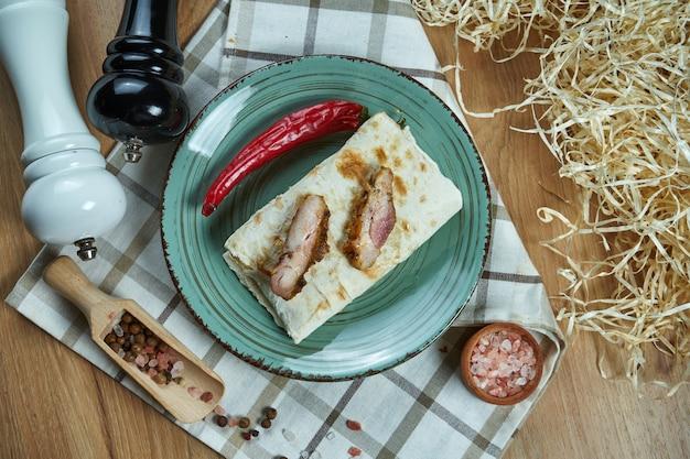 Pikantne burrito lub shawarma na niebieskim talerzu z tradycyjną wieprzowiną w kompozycji z przyprawami. zamknąć widok. zdjęcie jedzenia. leżał płasko