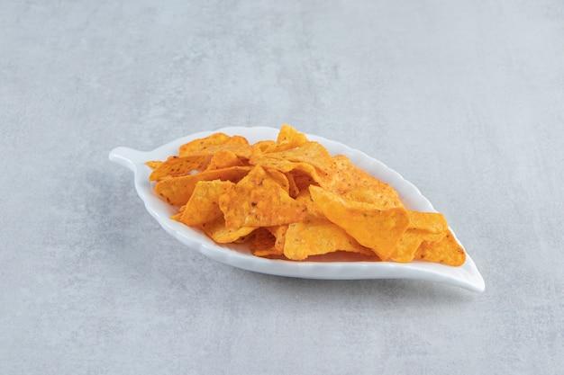 Pikantne chipsy tortilla na talerzu w kształcie liścia na kamieniu