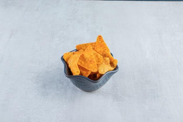 Pikantne chipsy tortilla w ciemnej misce na kamieniu.