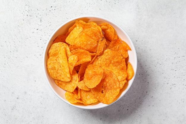 Pikantne chipsy ziemniaczane w białej misce, szare tło, widok z góry. koncepcja fast food.