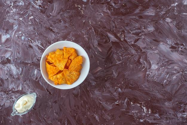 Pikantne chipsy ziemniaczane w misce i jogurt w szklance na marmurowym stole.