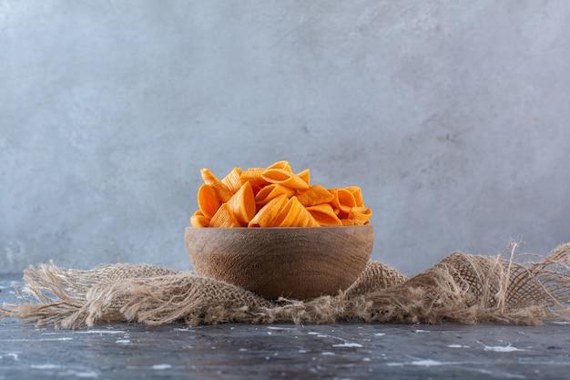 Pikantne chipsy ziemniaczane w misce na fakturze, na marmurowej powierzchni