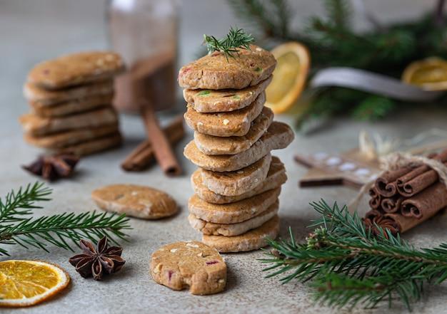 Pikantne ciasteczka maślane ułożone w stos z kandyzowanymi owocami, laskami cynamonu i anyżem.