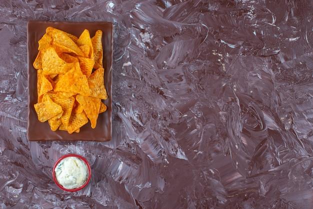 Pikantne frytki na talerzu obok miski majonezu, na marmurowym stole.
