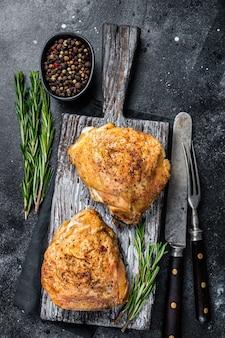 Pikantne grillowane udka z kurczaka na drewnianej desce z rozmarynem