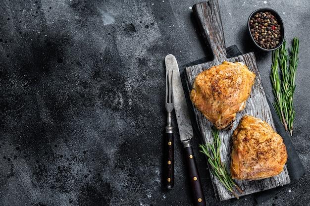 Pikantne grillowane udka z kurczaka z grilla na drewnianej desce z rozmarynem. widok z góry.