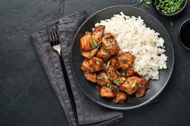 Pikantne kawałki fileta z kurczaka teriyaki z ryżem, zieloną cebulką i czarnym sezamem na czarnym talerzu