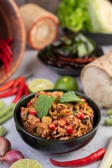 Pikantne kotlety wieprzowe w czarnej filiżance składającej się z cytryn chili i dodatków