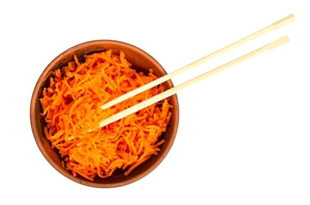 Pikantne marynowane marchewki w misce na białym talerzu
