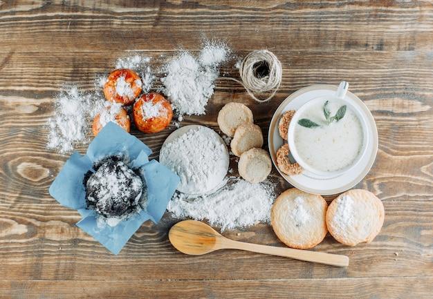 Pikantne mleko w filiżance z ciastkami, łyżką, liną, cukrem pudrem widok z góry na drewnianej powierzchni