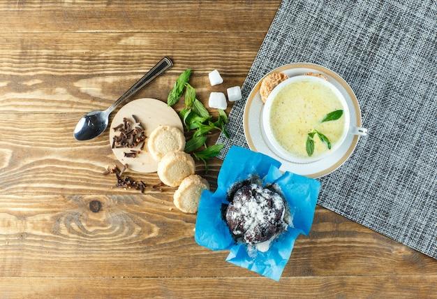 Pikantne mleko z miętą, łyżką, kostkami cukru, herbatnikami, goździkami w filiżance na drewnianym stole
