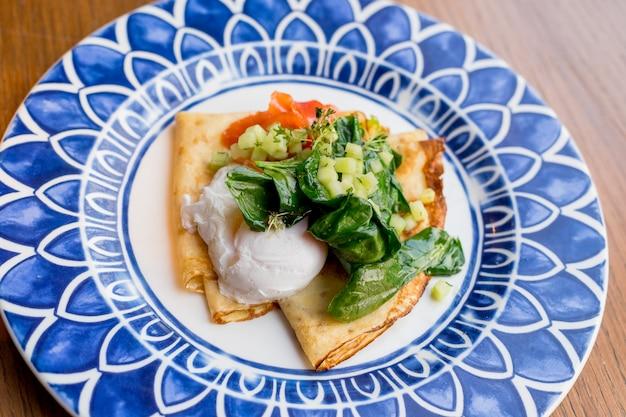 Pikantne naleśniki z łososiem i jajkiem w koszulce. smaczne śniadanie z naleśnikami, wędzonym łososiem, jajkiem w szpinaku, sałatą, cebulą, sosem holenderskim. świeże, zdrowe śniadanie.
