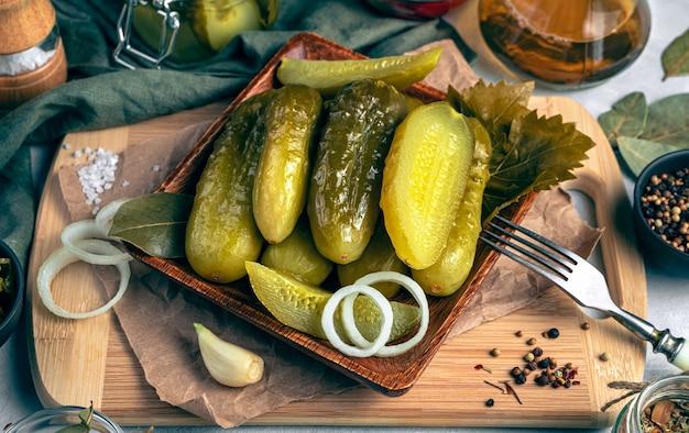 Pikantne ogórki kiszone z cebulą na drewnianej desce do krojenia na szarym tle. pojęcie tła kulinarnego.