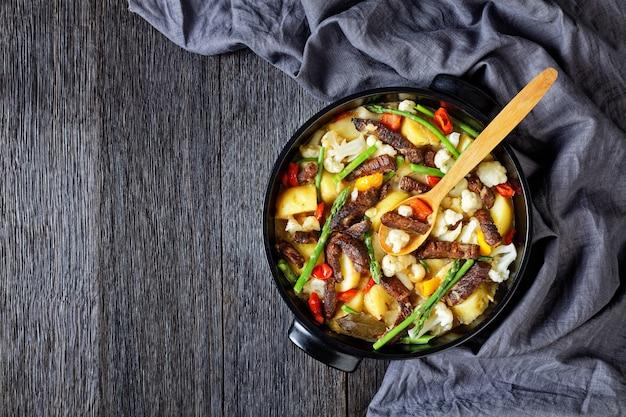 Pikantne paski wołowiny gulasz z nowymi ziemniakami, szparagami i kalafiorem w czarnym holenderskim piecu na drewnianym stole, kuchnia amerykańska, widok na krajobraz, leżakowanie na płasko, miejsce na kopię