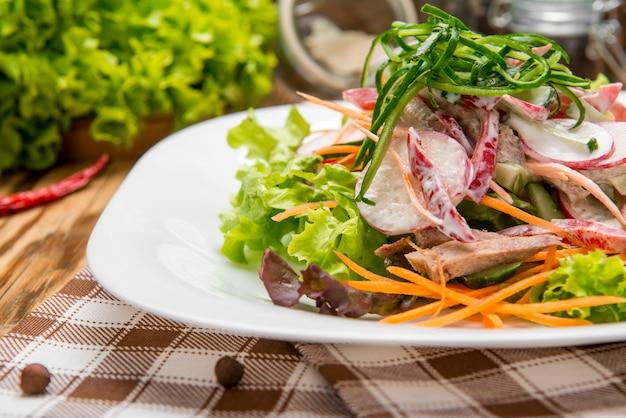 Pikantne plastry wołowiny sałatka mięsna z marchewką, pomidorami, ogórkiem, natką pietruszki, rzodkiewką i liśćmi szpinak, rukola, czerwony rubinowy chard na starym drewnianym stole