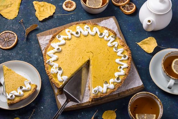 Pikantne pyszne okrągłe ciasto z dyni ozdobione białą śmietaną i pestkami dyni