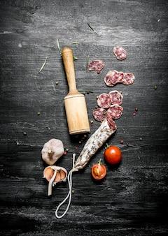 Pikantne salami z pomidorami i czosnkiem. na czarnej powierzchni rustykalnej.