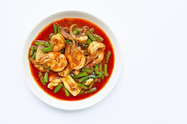 Pikantne smażone owoce morza i długa fasola z czerwoną pastą curry. tajskie jedzenie