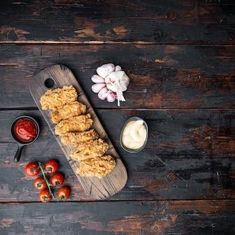 Pikantne smażone w głębokim tłuszczu panierowane skrzydełka z kurczaka kawałki na ciemnym drewnianym stole, płaskie.