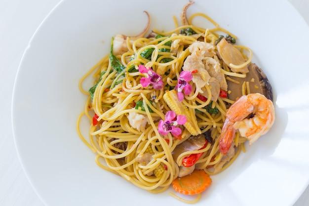 Pikantne spaghetti z owocami morza (np. krewetkami, kalmarami i wieprzowiną) i bazylią na białym talerzu.