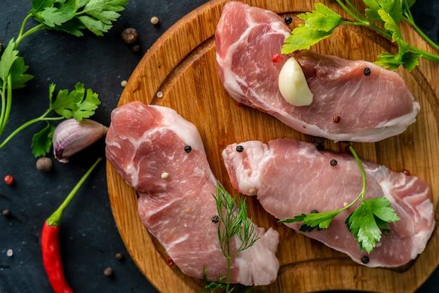 Pikantne surowe mięso na drewnianej desce do krojenia lub krojenia, włóż sól na niegotowane mięso