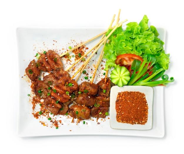 Pikantne szaszłyki wieprzowe z jelita wieprzowego chińskie przyprawy udekoruj warzywa i zanurzaj na sucho sos przyprawowy widok z góry