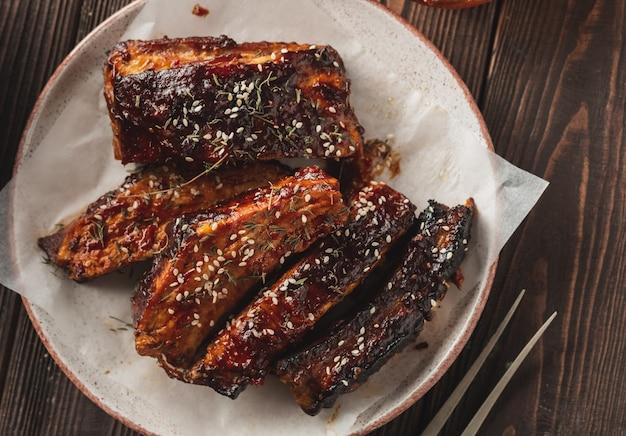 Pikantne żeberka z grilla podawane na drewnianym stole. wędzone pieczone żeberka wieprzowe.