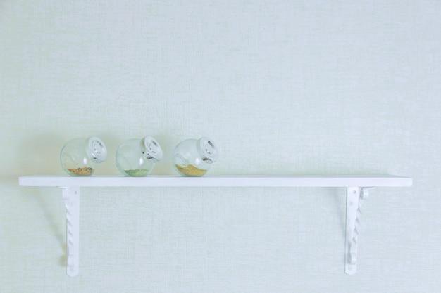 Pikantność w butelkach na białej drewnianej półce. copyspace.
