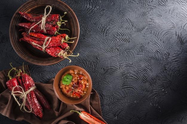 Pikantny chili na ciemnym tle w ceramicznych talerzach