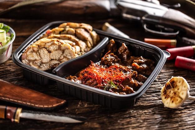 Pikantny i pyszny gulasz z jelenia z dziczyzny zapakowany w przenośne plastikowe pudełko na wynos. jedzenie podawane jest z domowymi kluskami. lunch otoczony jest rustykalną strzelbą, kulami i nożem myśliwskim.