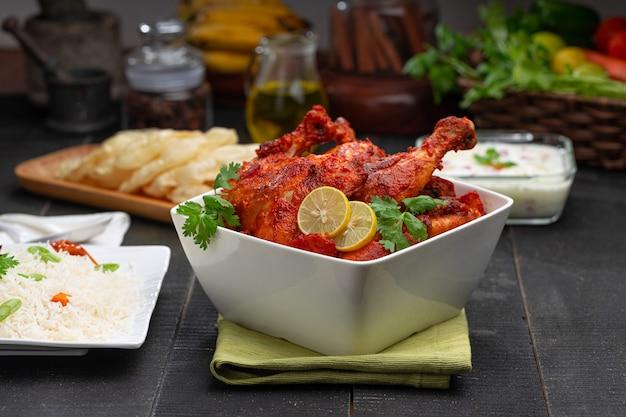 Pikantny kurczak tandoori przyozdobiony liściem kolendry w białej misce w kształcie kwadratu