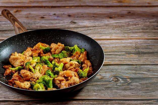 Pikantny kurczak teriyaki z brokułami na patelni na drewnianym tle rustykalnym.