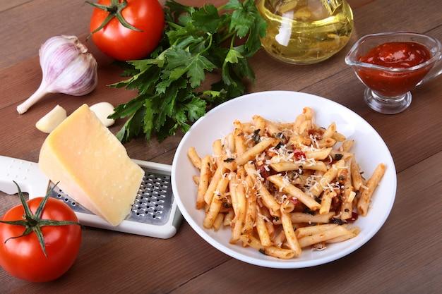 Pikantny makaron penne bolognese z warzywami, chili i serem w sosie pomidorowym.
