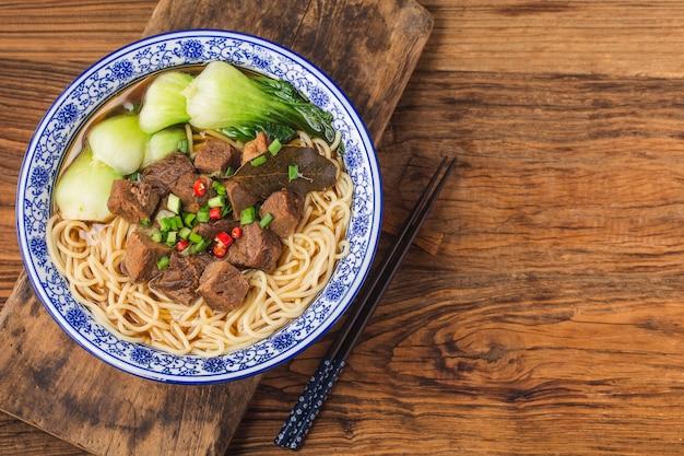 Pikantny makaron wołowy z czerwoną zupą w misce na drewnianym stole