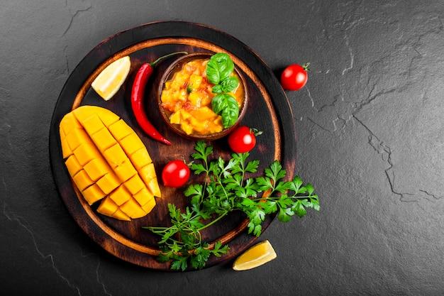Pikantny meksykański sos salsa z mango, chili, pomidorami i bazylią w drewnianej misce