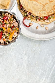 Pikantny naleśnik gryczany z białą fasolą, czerwoną i żółtą papryką, pietruszką i kurczakiem. meksykańska quesadilla. widok z góry. skopiuj miejsce