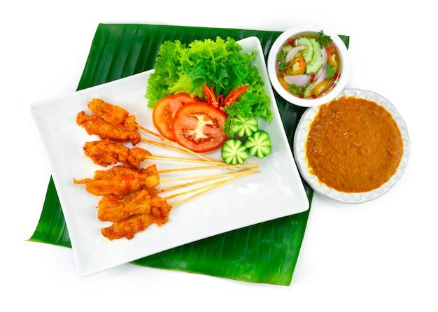 Pikantny satay wieprzowy lub pikantna grillowana wieprzowina w szaszłykach podana maczany sos orzechowy chili, sos słodko-kwaśny dekoracja dania tajskiej przystawki z rzeźbionymi warzywami widok z góry