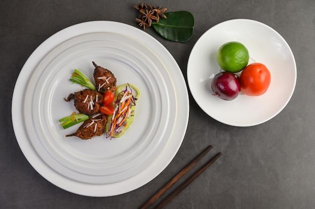Pikantny smażony mieszać sum na białym talerzu z pałeczkami. tajskie jedzenie.