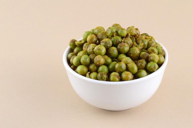 Pikantny smażony zielony groszek {chatpata matar} indyjska przekąska. suszony solony zielony groszek