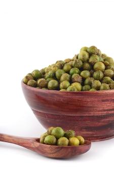 Pikantny smażony zielony groszek {chatpata matar} indyjska przekąska. wysuszony solony zielony groszek w drewnianym pucharze z łyżką na białym tle