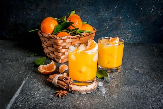 Pikantny zimowy koktajl mandarynkowy z wódką, świeżymi mandarynkami, cynamonem i anyżem, na ciemnym tle, miejsce