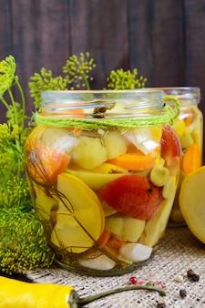 Pikle: asortyment warzyw (cukinia, papryka, marchew, pomidor, zielony groszek) w szklanych słoikach na ciemnym drewnianym.