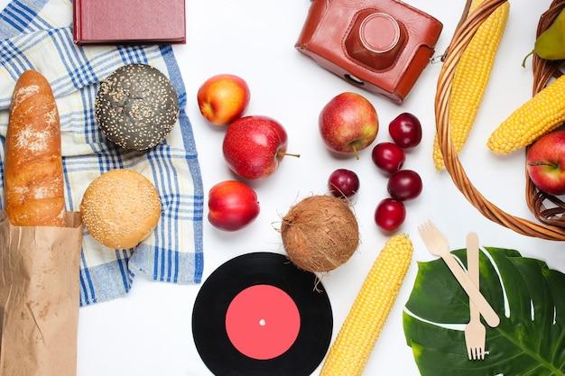 Piknik francuski w stylu retro. kosz z owocami i warzywami, retro aparat, książka, bagietka i inne jedzenie piknikowe białe tło. widok z góry. strzał studio