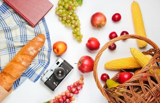 Piknik francuski w stylu retro. kosz z owocami i warzywami, retro aparat, książka, bagietka i inne jedzenie piknikowe białe tło.