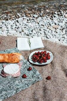 Piknik na kratę z bagietką wiśnie ser otwarta książka