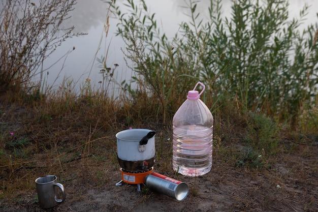 Piknik na łonie natury. palnik gazowy i kubek gorącej herbaty.