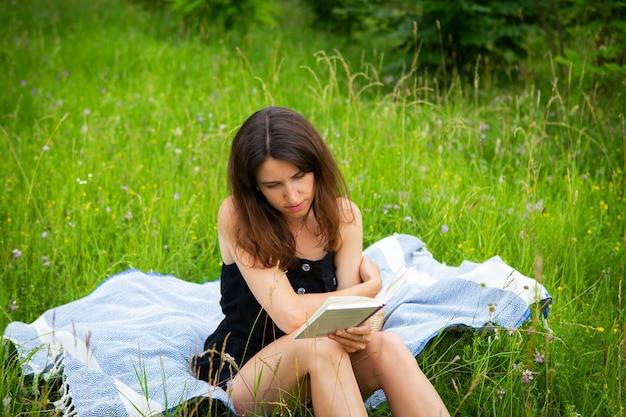 Piknik na świeżym powietrzu. dziewczyna czyta książkę na świeżym powietrzu siedząc na niebieskiej kratę. dziewczyna cieszy się świeżym powietrzem. rekreacja na świeżym powietrzu, zbliżenie.