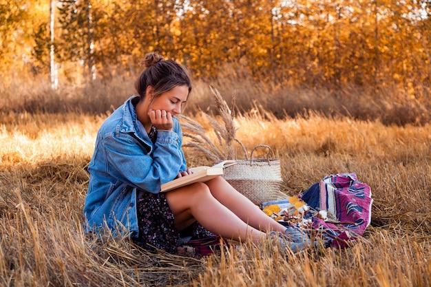 Piknik na świeżym powietrzu: młoda kobieta w dżinsowej kurtce i sukience czyta książki na kratce z koszem piknikowym, jabłkami, winem.